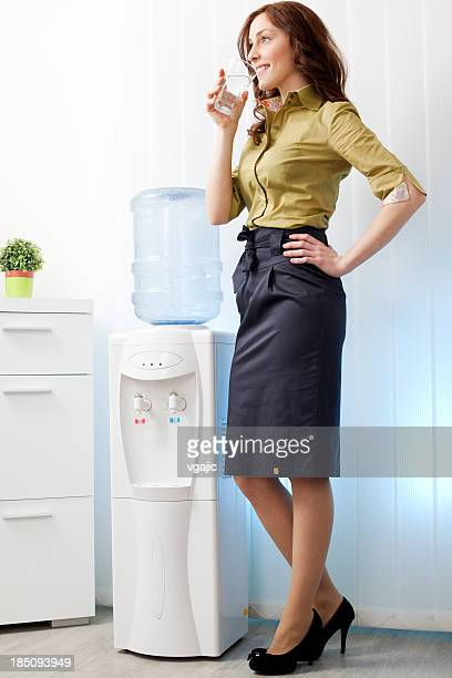 Businesswoman having drink from Water cooler