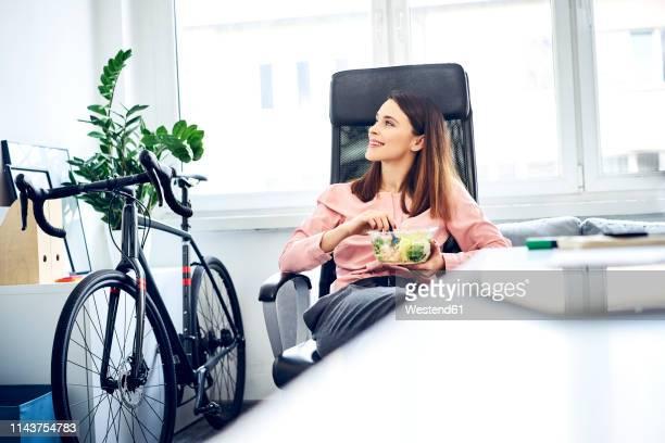 businesswoman having lunch break in office sitting at desk - mittagessen stock-fotos und bilder