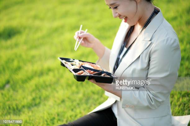 businesswoman having lunch in park - lunch break stock photos and pictures