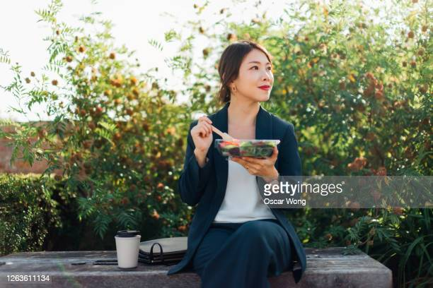 businesswoman having taking a lunch break outdoors - working stock pictures, royalty-free photos & images