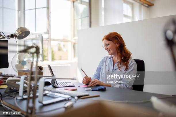businesswoman having teleconference from her desk - business stock pictures, royalty-free photos & images