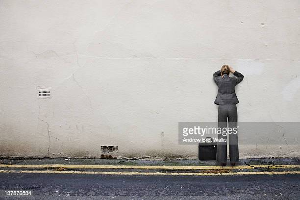 Businesswoman head in hands facing a wall