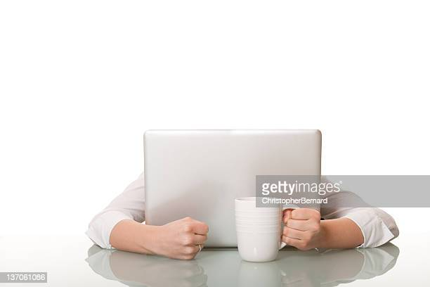 Businesswoman hiding behind her computer with coffee cup