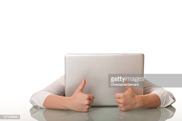 Businesswoman hiding behind her computer with thumbs up