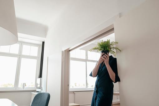 Businesswoman hiding behind plant in office - gettyimageskorea
