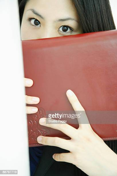 Businesswoman hiding her face with a diary