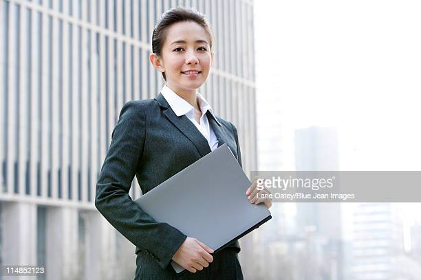 Businesswoman holdig a folder of documents, downtown