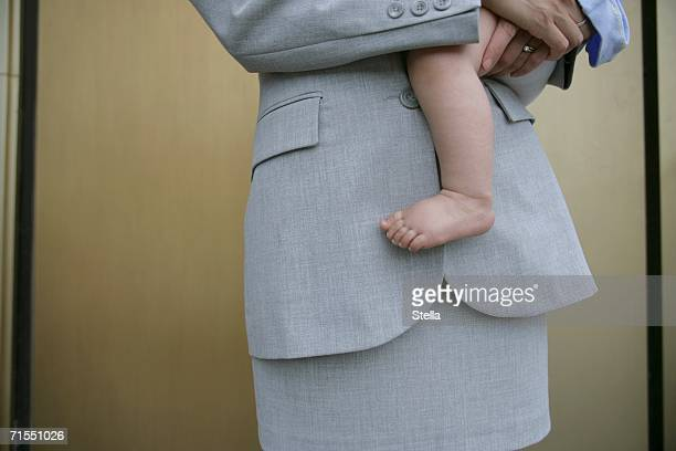 A businesswoman holding a baby