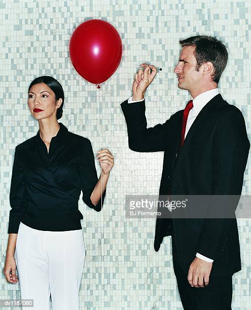 Businesswoman Holding a Balloon and a Businessman Next to Her Holding a Pin