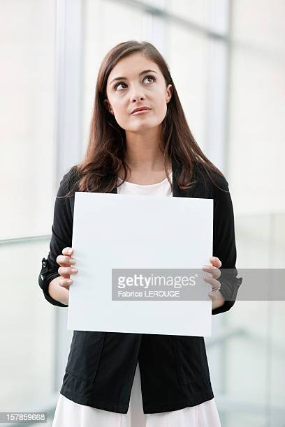 Businesswoman holding a blank placard and thinking in an office