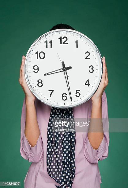 businesswoman holding a clock in front of her face - fular fotografías e imágenes de stock
