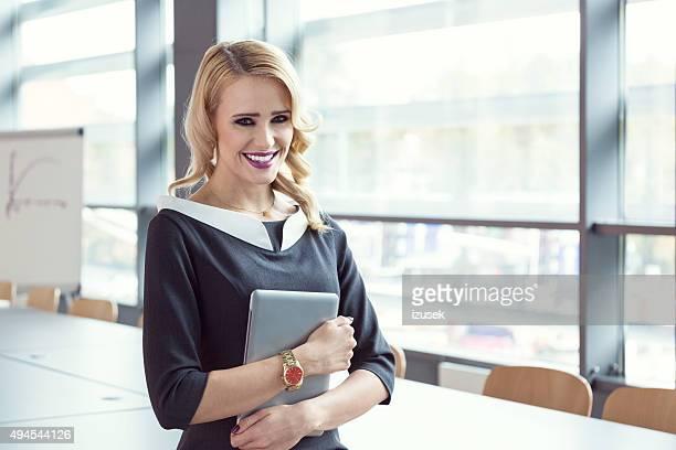 Geschäftsfrau holding digital tablet stehen im Meetingraum