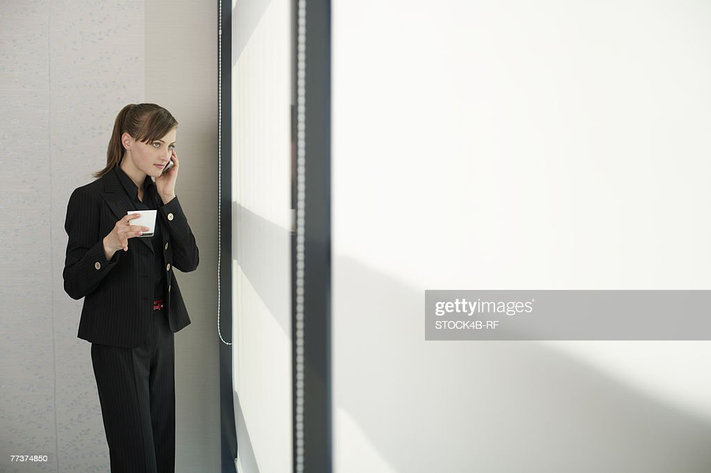 Businesswoman holding a glass while phoning with a mobile phone : Photo