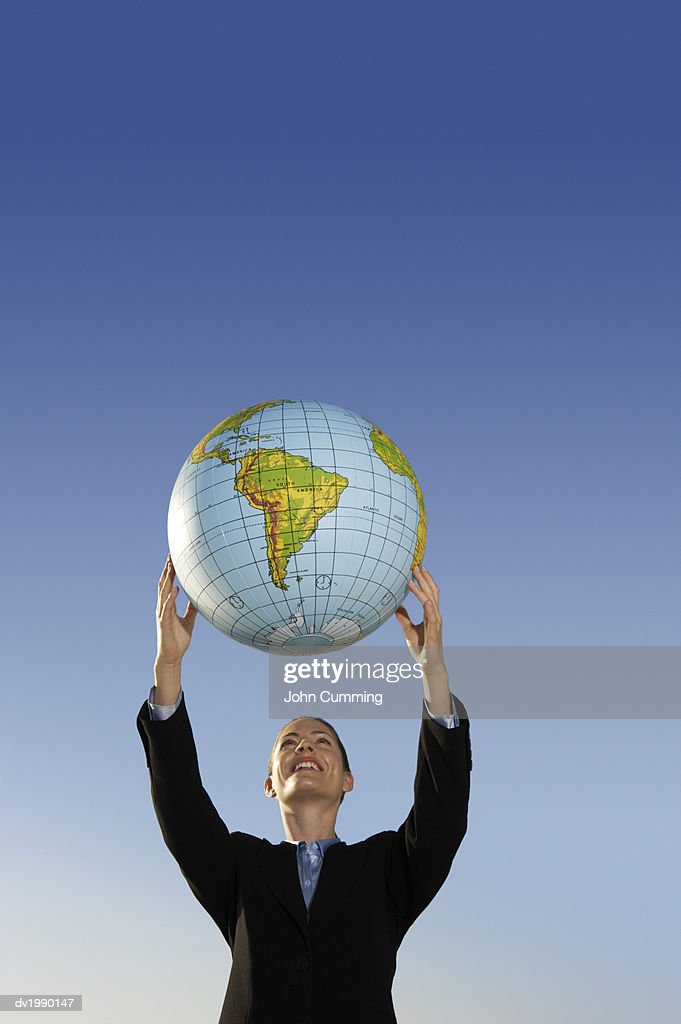Businesswoman Holding a Globe Above Her : Stock Photo