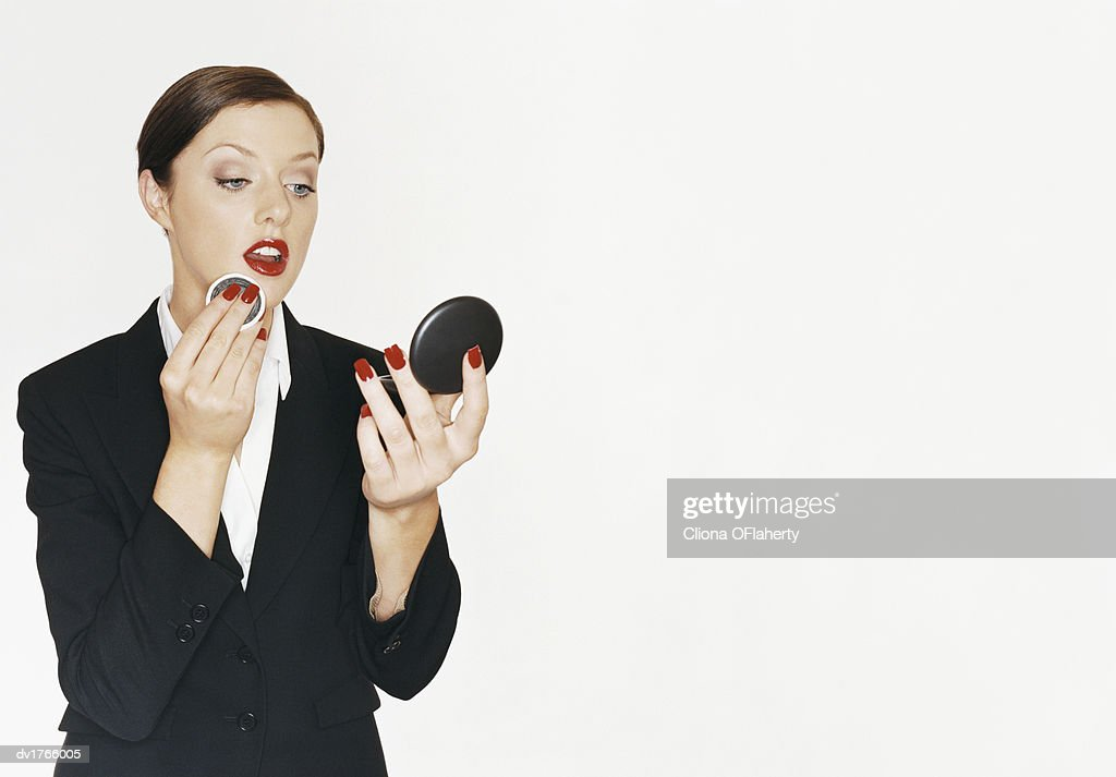 Businesswoman Holding A Hand Mirror And Applying Foundation On Her