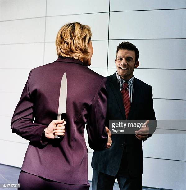 Businesswoman Holding a Knife Behind Her Back Greets a Businessman