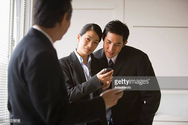 Businesswoman holding a mobile phone with two businessmen standing beside her