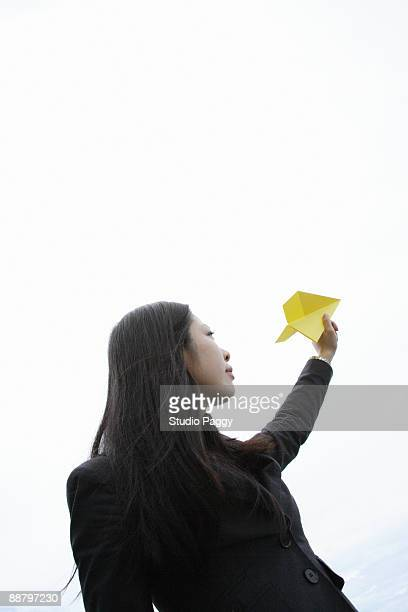Businesswoman holding a paper airplane