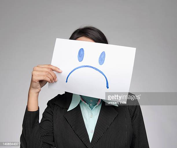Businesswoman holding a sad face in front of her face