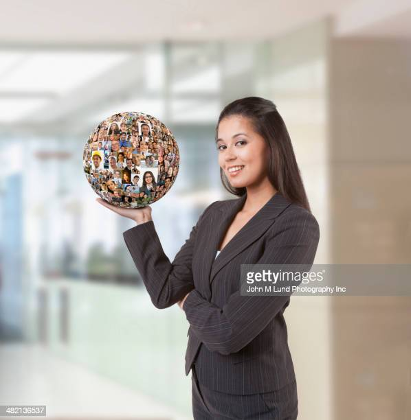 Businesswoman holding ball of business people's faces