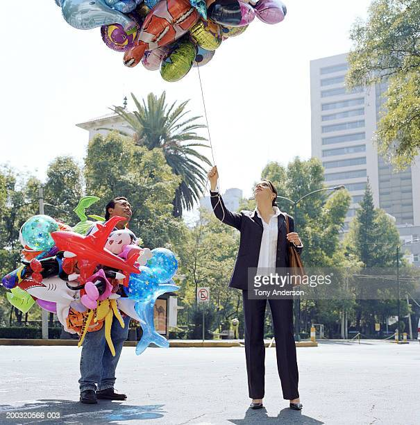 Businesswoman holding balloons purchased from vendor