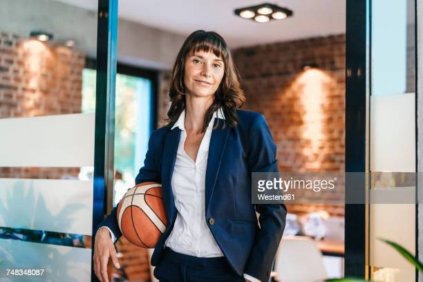 businesswoman holding basket ball in office - fair play sport foto e immagini stock
