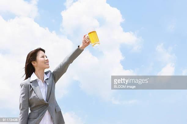 Businesswoman holding beer mug