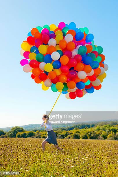 businesswoman holding big bunch of balloons