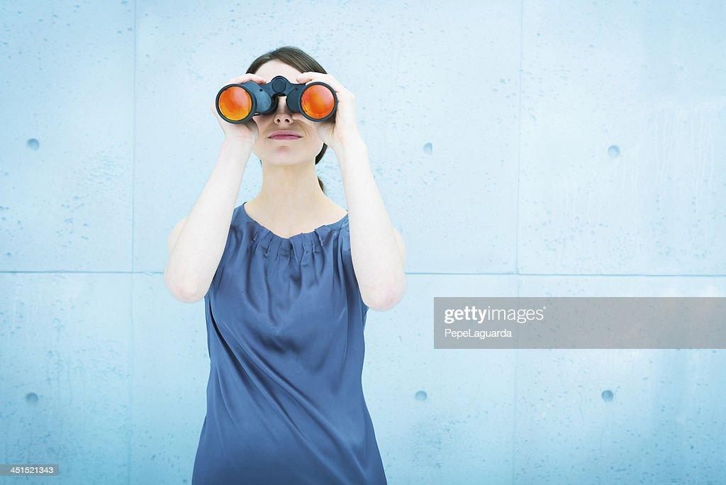 Businesswoman holding binoculars : Stock Photo