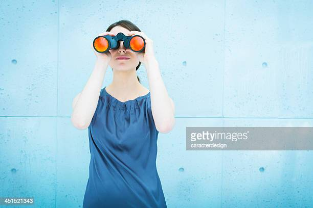 Businesswoman holding binoculars