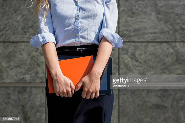 Businesswoman holding book and digital tablet outdoors