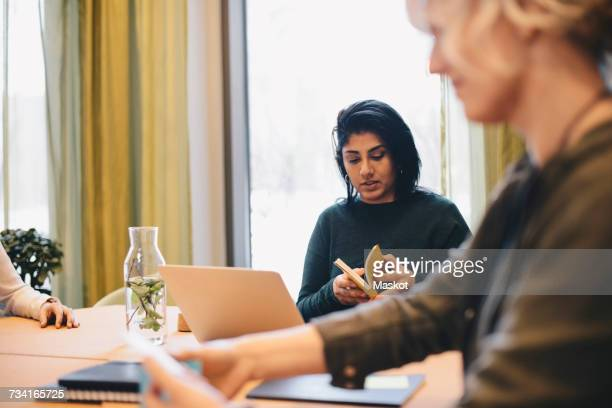 Businesswoman holding book while sitting with colleague at desk in board room