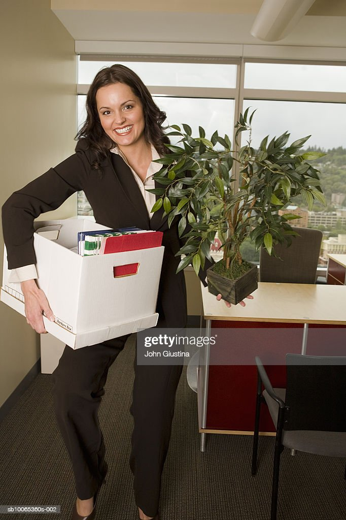 Businesswoman holding box and pot plant, smiling, portrait : Foto stock