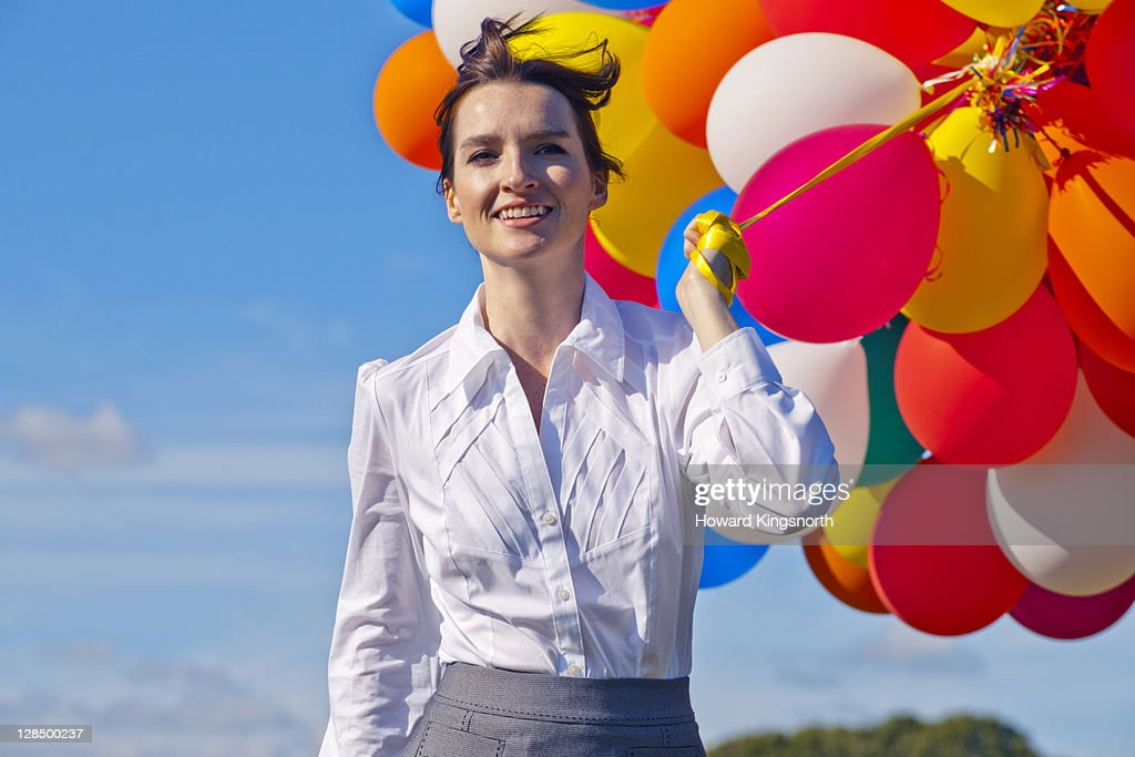 businesswoman holding bunch of balloons : Stock Photo