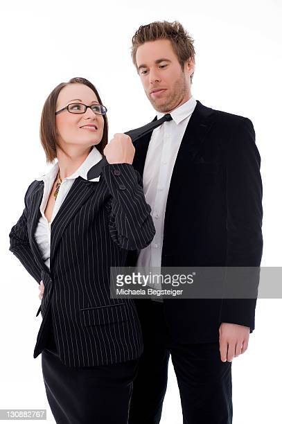 Businesswoman holding businessman by his tie, emancipation in work