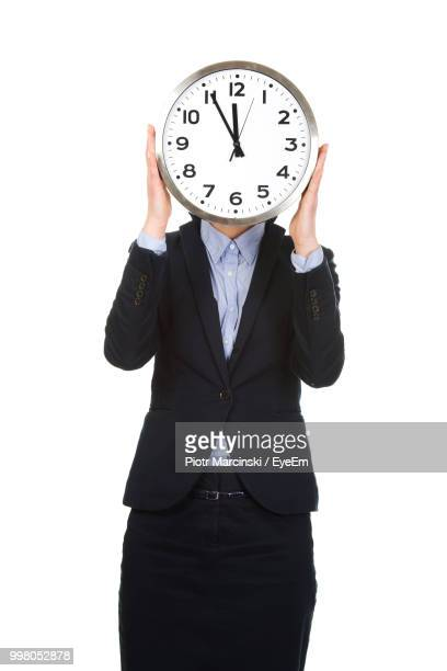 businesswoman holding clock in front of face against white background - cadran d'horloge photos et images de collection