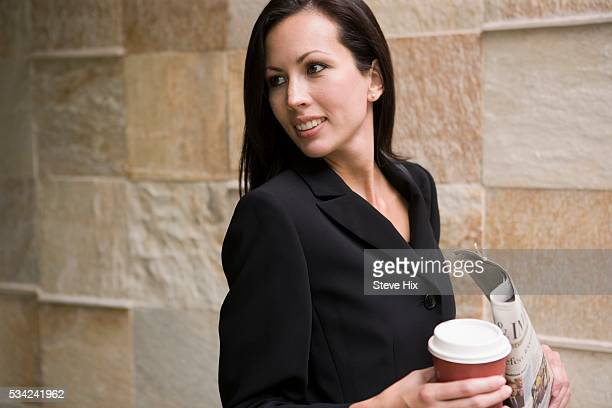 Businesswoman Holding Coffee and a Newspaper