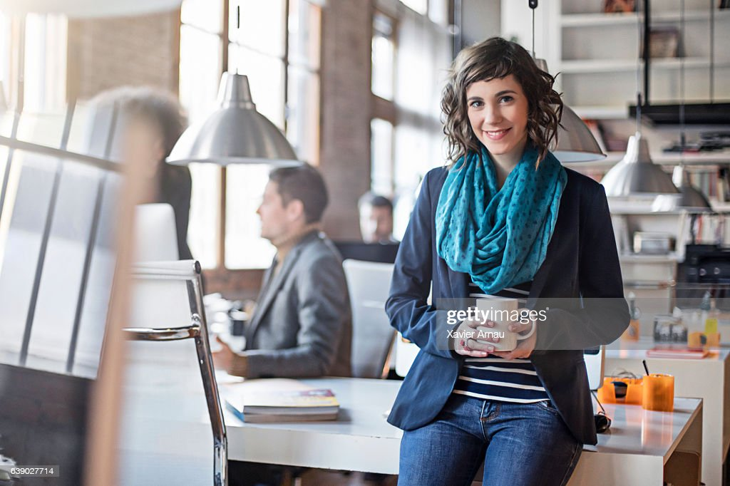 Businesswoman holding coffee cup in office : Stock Photo