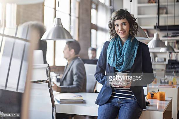 businesswoman holding coffee cup in office - three quarter front view stock pictures, royalty-free photos & images