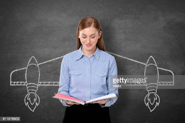 Businesswoman holding diary in front blackboard