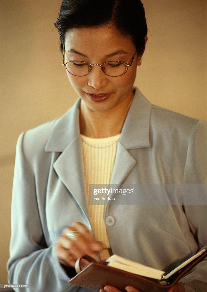 Businesswoman holding diary, portrait : Stock Photo