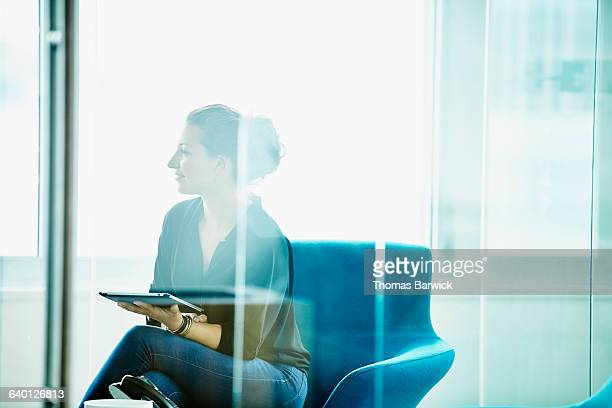 businesswoman holding digital tablet in meeting - frau bluse durchsichtig stock-fotos und bilder
