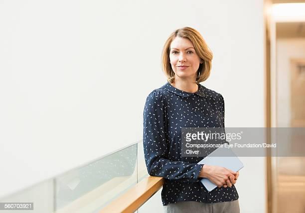 Businesswoman holding digital tablet on walkway