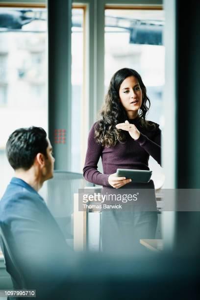businesswoman holding digital tablet presenting data during project meeting in office - vertical stock-fotos und bilder