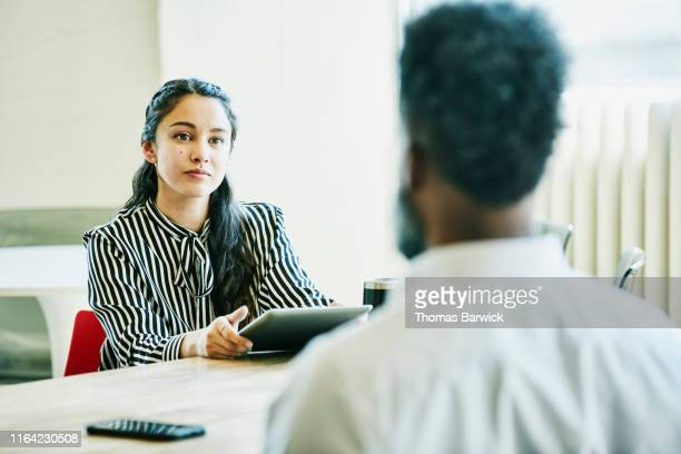 Businesswoman holding digital tablet working with client in office conference room