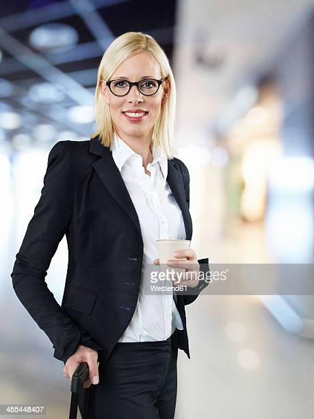 Businesswoman holding disposable cup and briefcase at airport, smiling