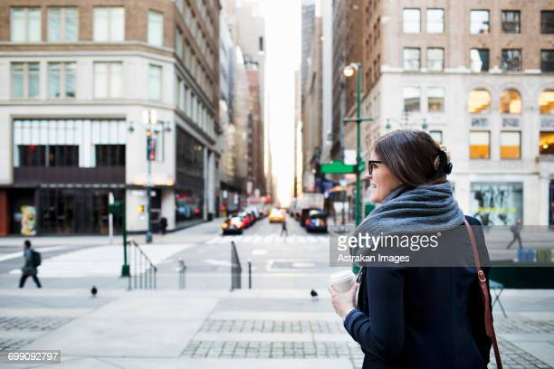 businesswoman holding disposable cup while waiting by road in city - bryant park stock pictures, royalty-free photos & images