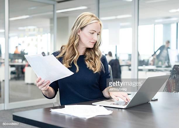 Femme d'affaires tenant document et à l'aide d'un ordinateur portable dans le bureau moderne