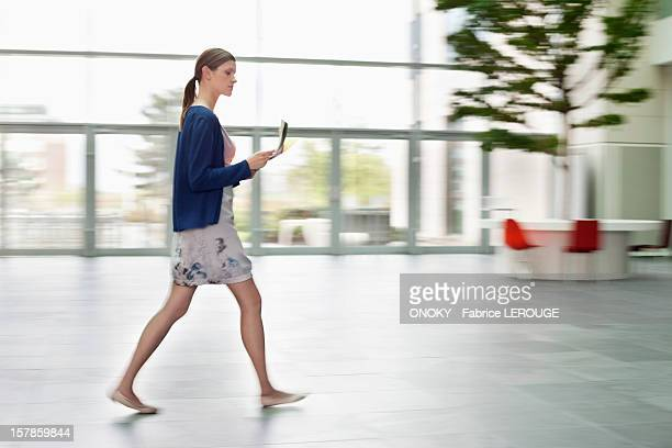 Businesswoman holding documents and walking in an office lobby