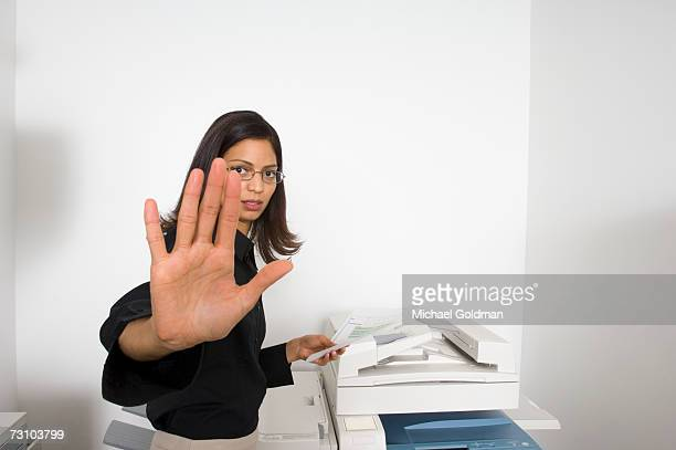 Businesswoman holding documents by photocopier, focus on hand